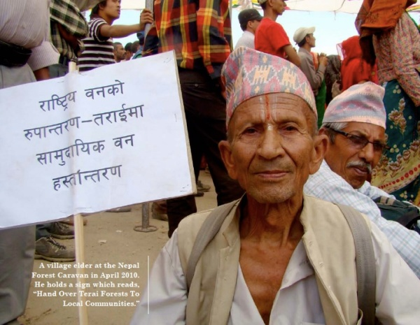 """A village elder at the Nepal Forest Caravan in April 2010. He holds a sign which reads, """"Hand Over Terai Forests to Local Communities"""""""