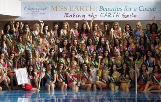 Candidates of the Miss Earth beauty contest hold tree seedlings and placards promoting environmental advocacy in Manila