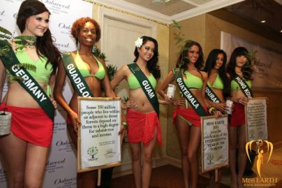 Miss Earth contestants hold banners with forest facts